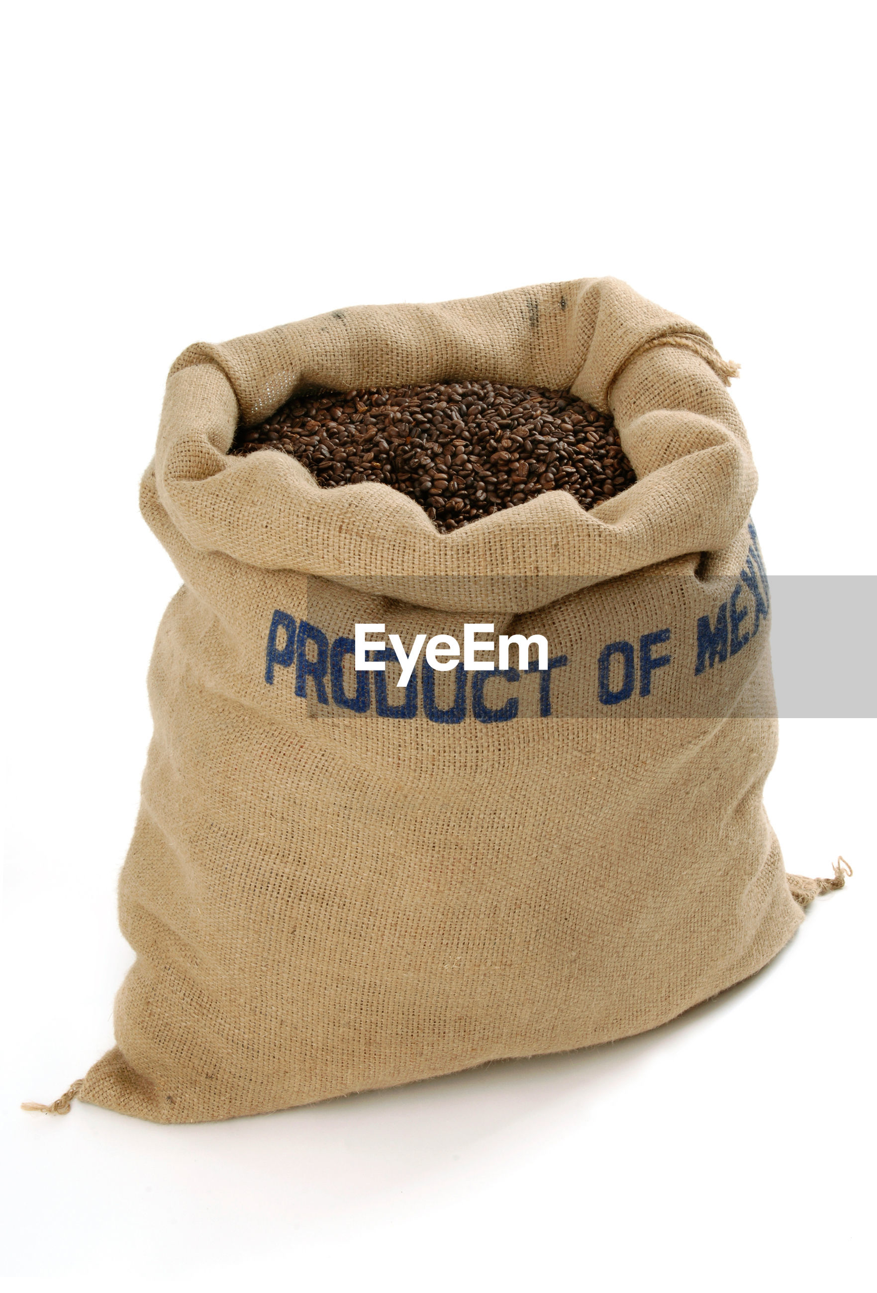 Close-up of roasted coffee beans in sack over white background