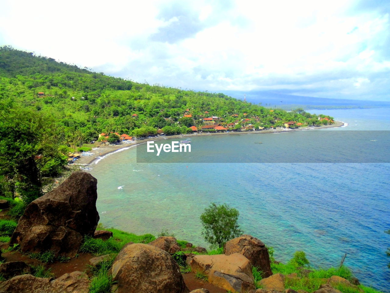 Scenic View Of Sea And Green Hill Against Sky