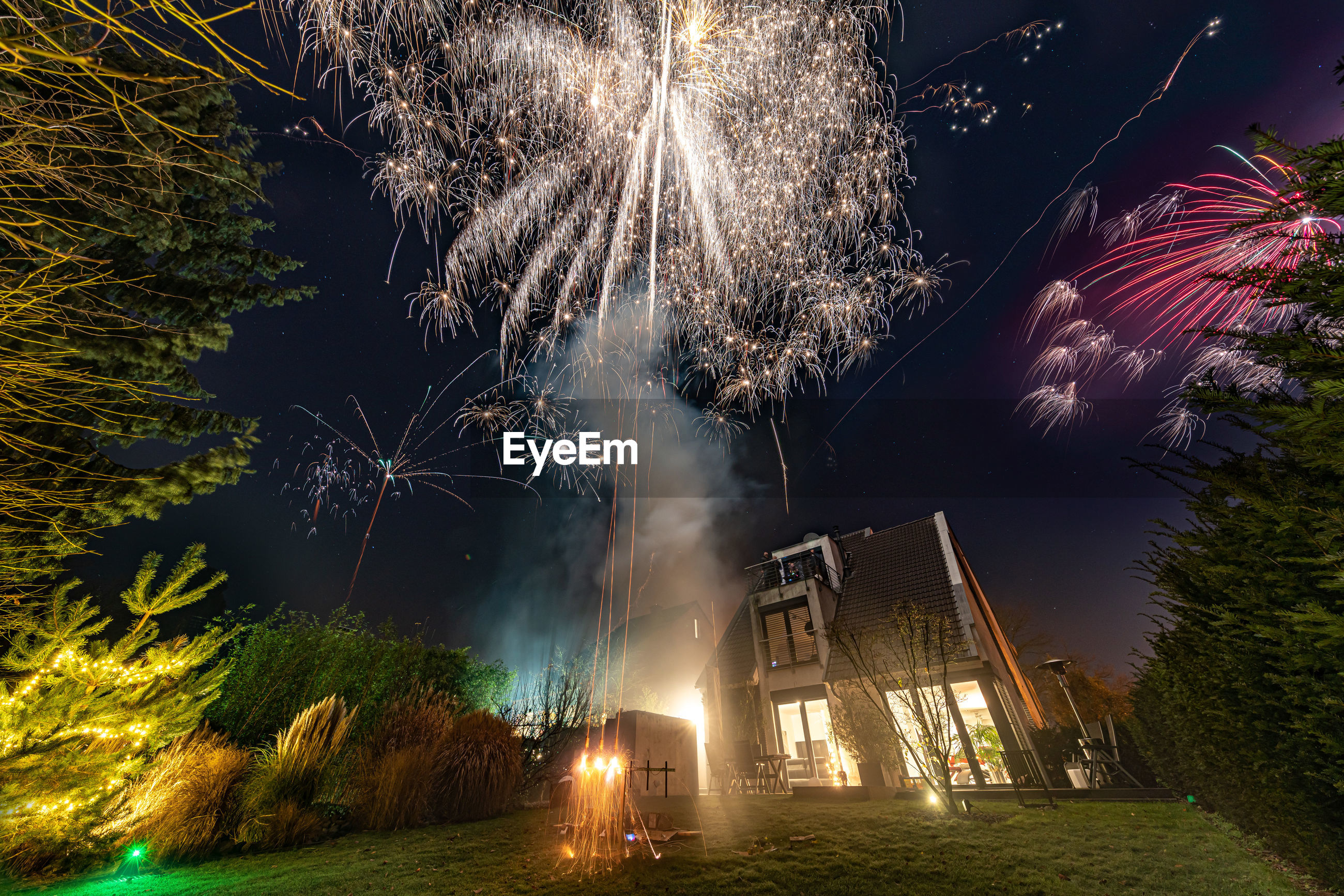 FIREWORK DISPLAY OVER TREES AGAINST SKY AT NIGHT