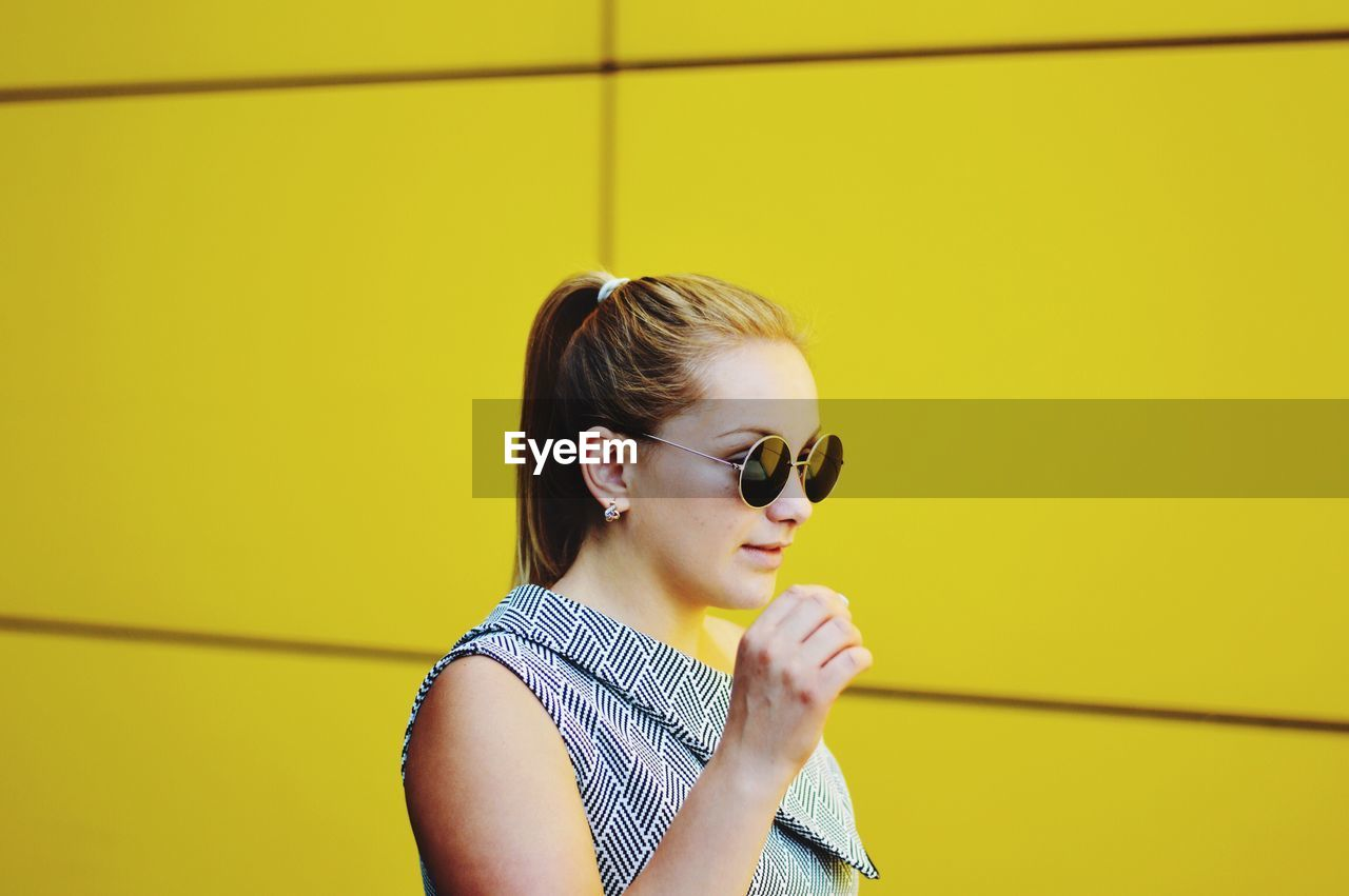 Young Woman Wearing Sunglasses Standing Against Yellow Wall