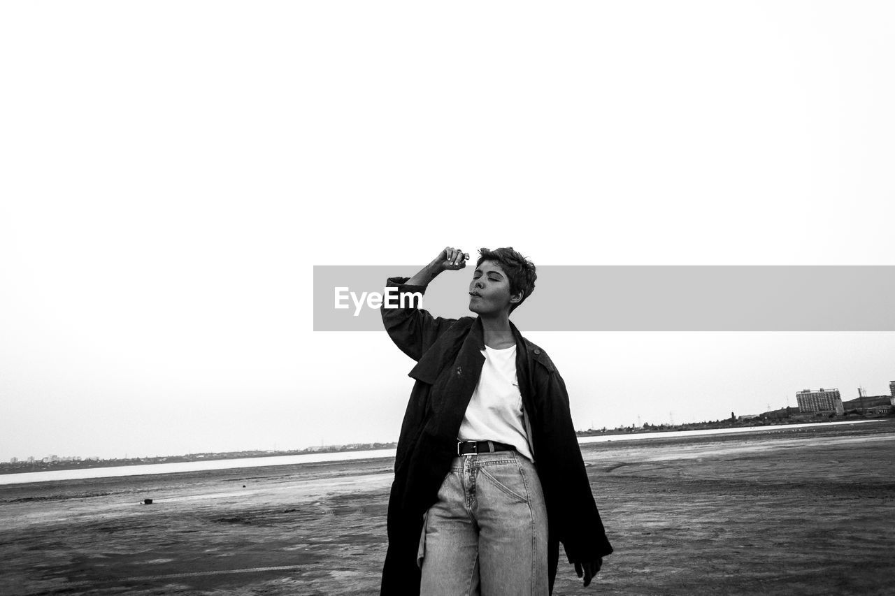 real people, leisure activity, one person, standing, beach, front view, casual clothing, young adult, outdoors, lifestyles, clear sky, sea, holding, young women, sky, day, nature, water, people