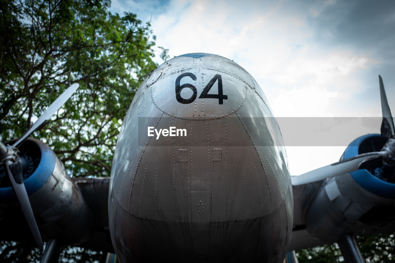 cloud - sky, day, mode of transportation, number, no people, nature, text, sky, transportation, metal, outdoors, communication, tree, close-up, air vehicle, western script, plant, focus on foreground, airplane, low angle view