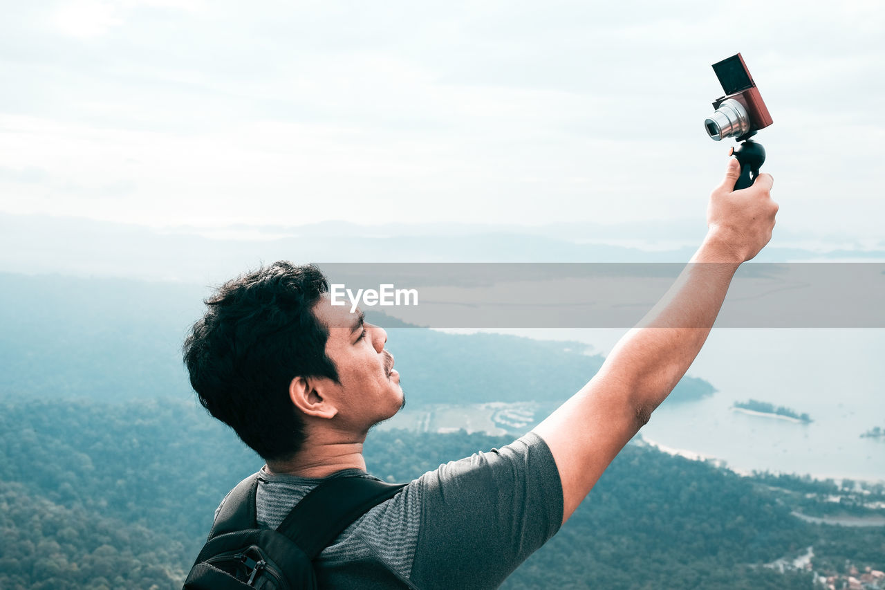 Young man talking selfie against clear sky