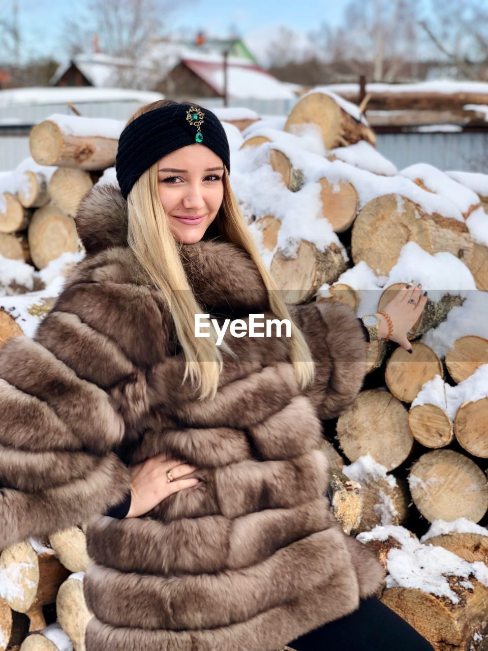 Portrait of smiling young woman wearing warm clothing by woodpile during winter