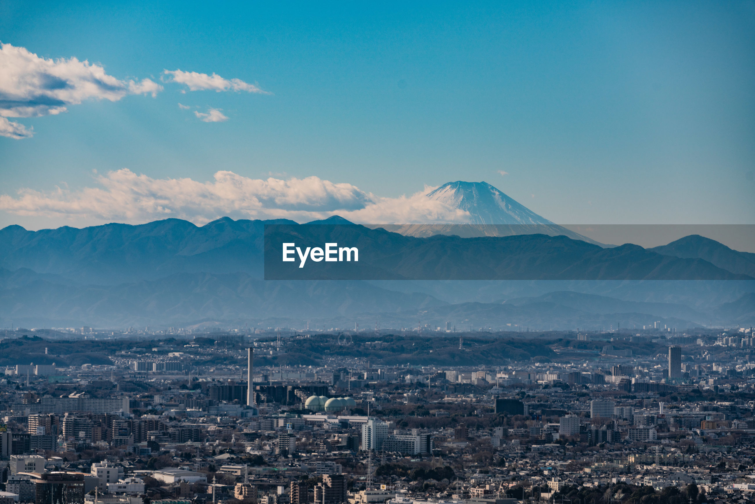 AERIAL VIEW OF CITYSCAPE AGAINST MOUNTAINS