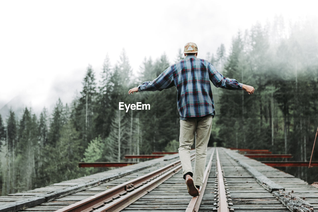 REAR VIEW OF MAN STANDING ON RAILROAD TRACK AGAINST TREES