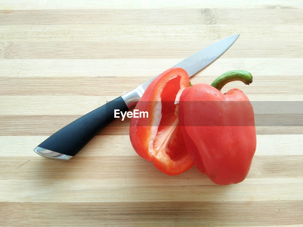 food and drink, food, table, healthy eating, pepper, red, still life, vegetable, wellbeing, freshness, cutting board, kitchen knife, indoors, wood - material, high angle view, no people, close-up, chili pepper, bell pepper, knife, chopped