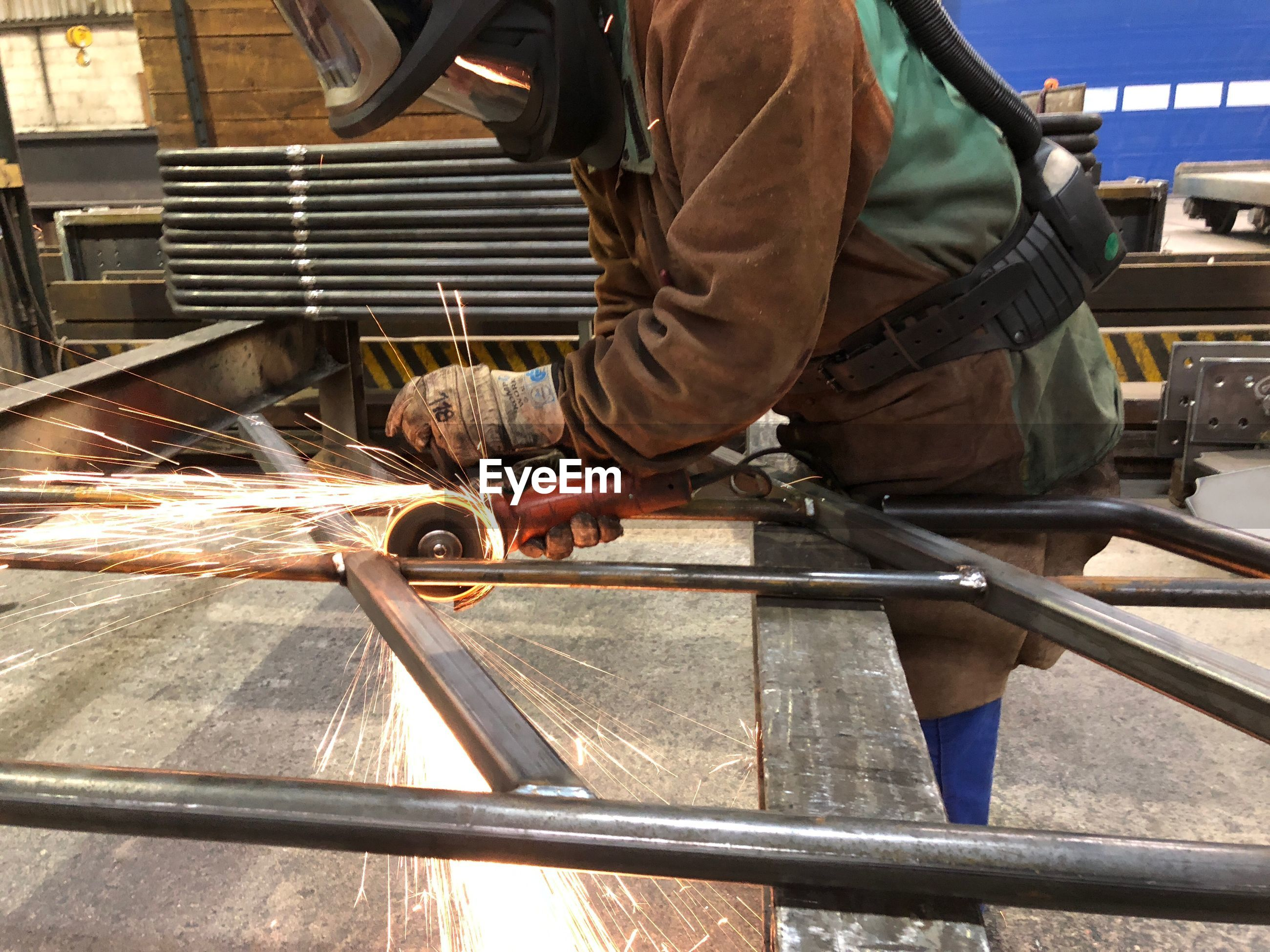Man grinding metal in factory