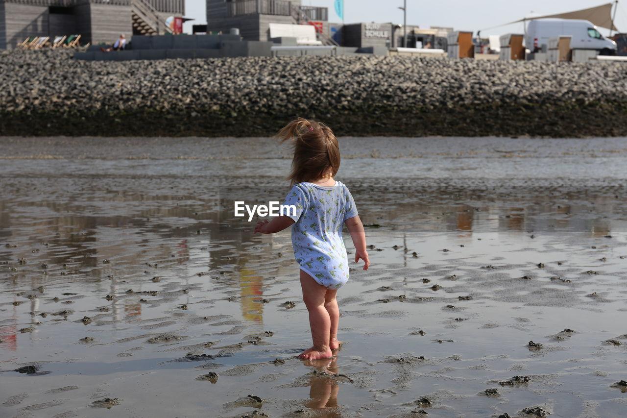 Rear view of toddler walking on beach