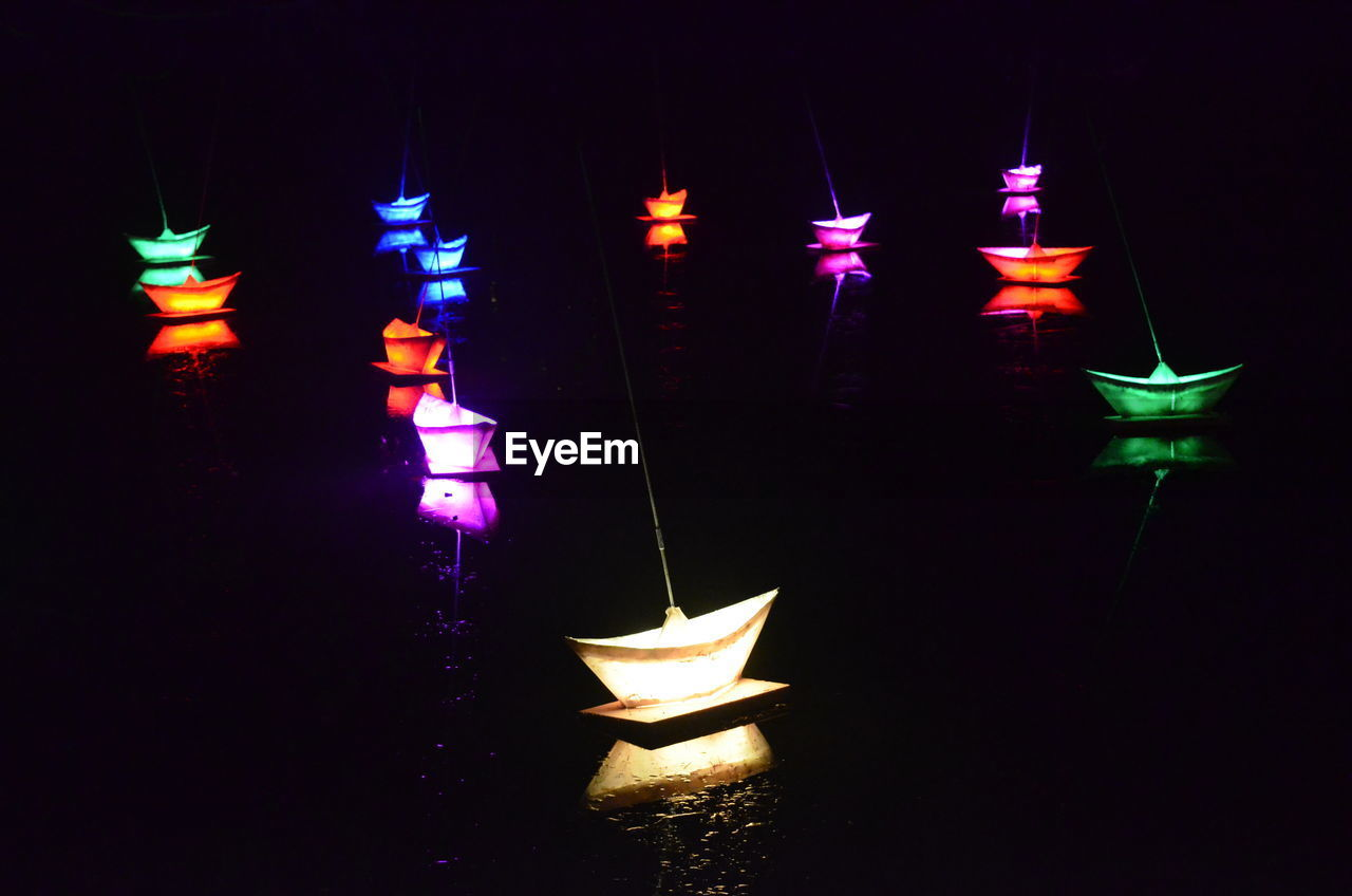 Close-Up Of Illuminated Paper Boats Against Black Background