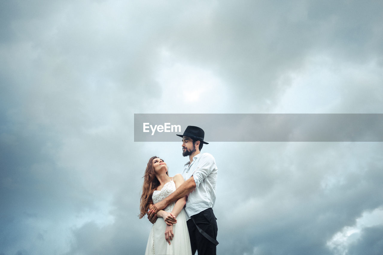 Low Angle View Of Man Embracing Woman While Standing Against Cloudy Sky