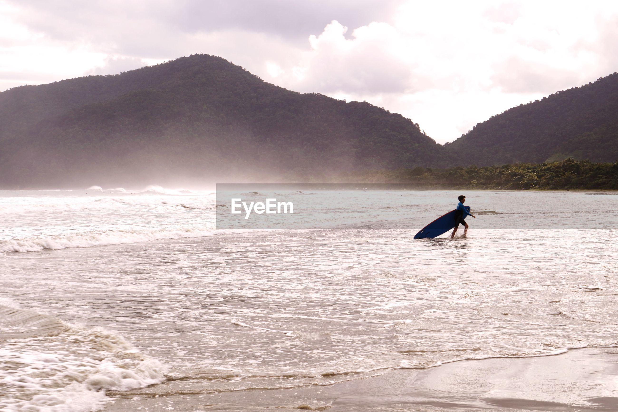 Boy surfing in sea against sky