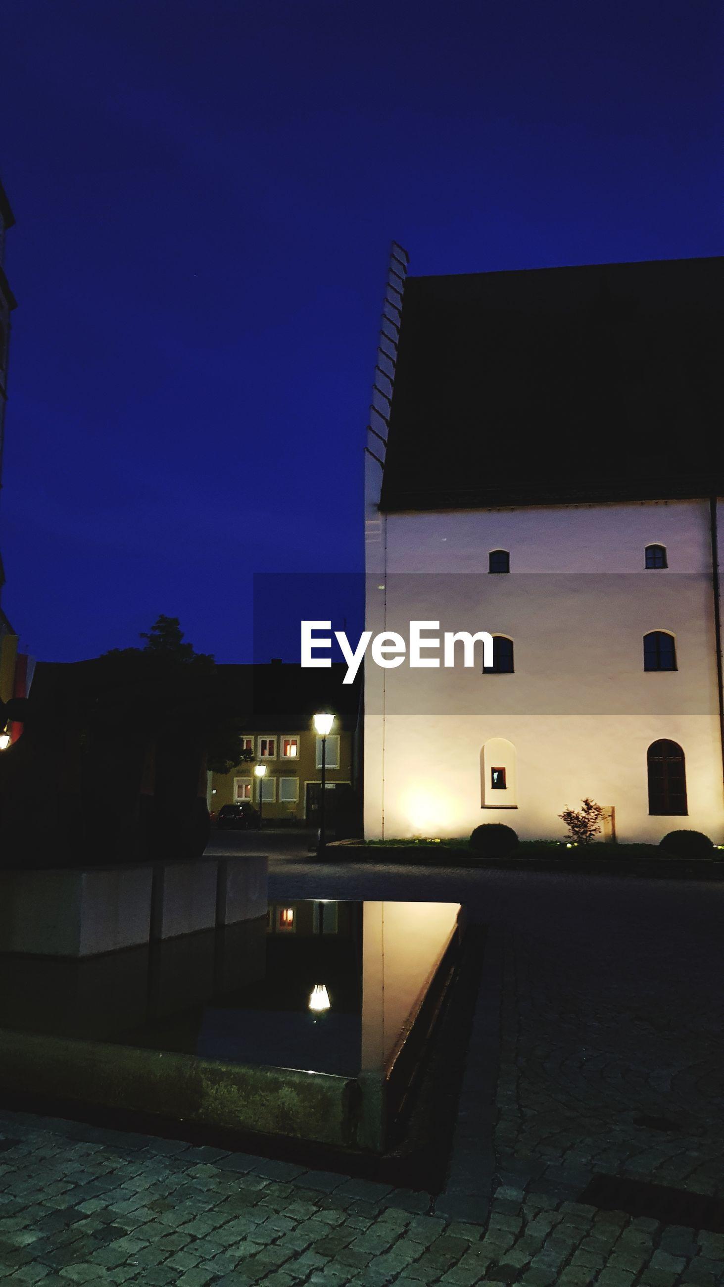 ILLUMINATED BUILDINGS AGAINST BLUE SKY AT NIGHT