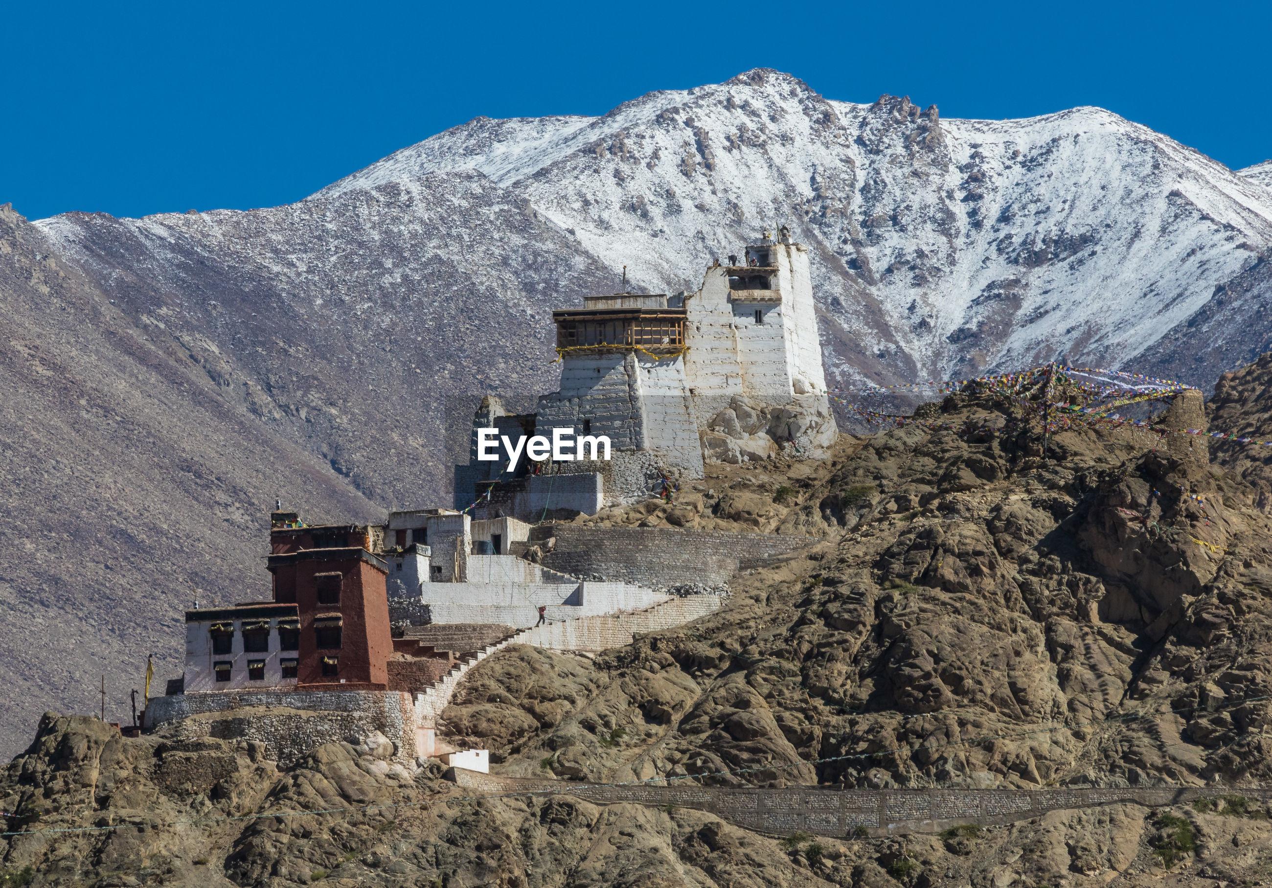 Castle against snowcapped mountains