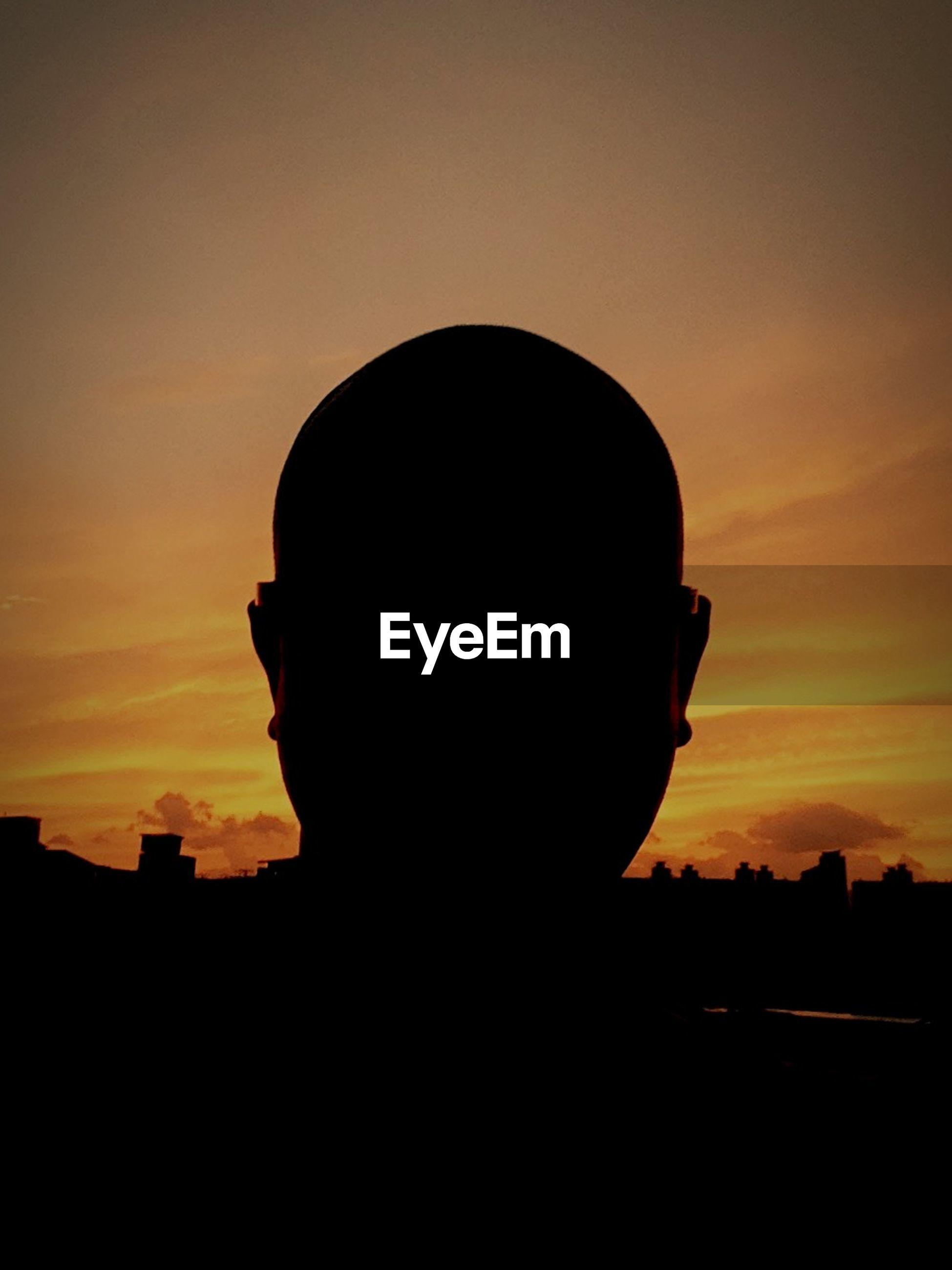 silhouette, sunset, sky, lifestyles, leisure activity, orange color, headshot, waist up, standing, men, built structure, side view, outdoors, cloud - sky, dark, low angle view, contemplation, dusk