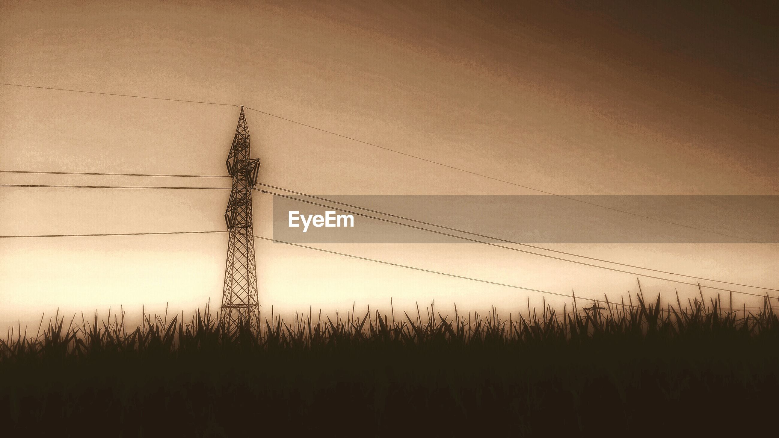 Silhouette of electricity pylon at dusk