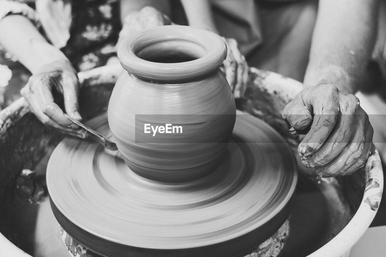 Cropped Hands Of Potter Making Pot At Workshop