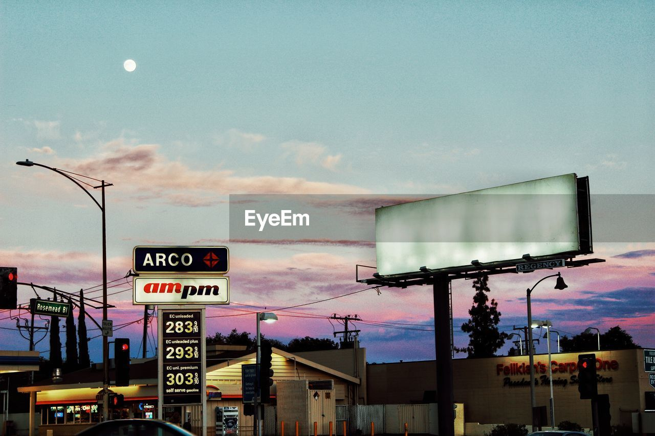 communication, sky, text, illuminated, cloud - sky, outdoors, architecture, dusk, sunset, built structure, road sign, transportation, building exterior, no people, low angle view, day, city, nature