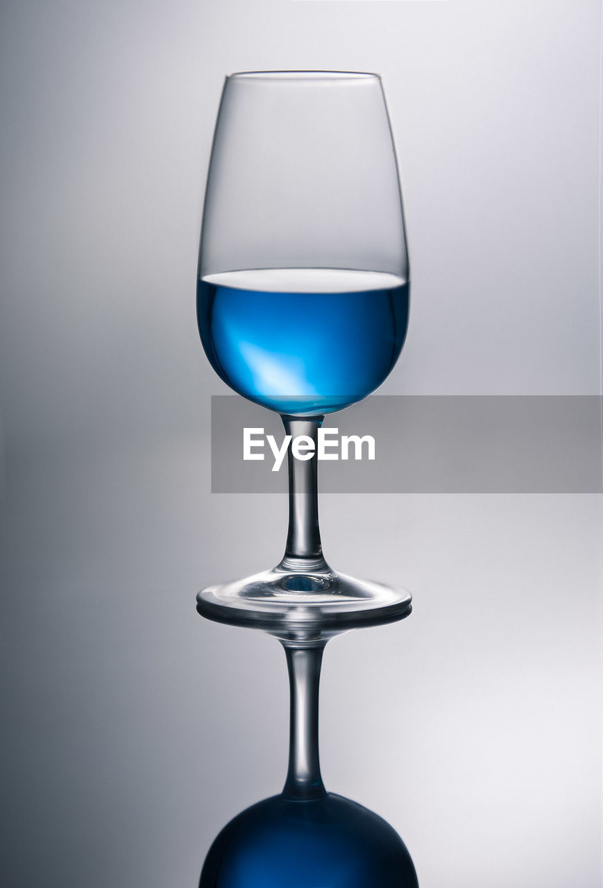 indoors, no people, studio shot, transparent, blue, gray background, close-up, glass - material, glass, wineglass, single object, gray, still life, refreshment, household equipment, table, reflection, food and drink, drink