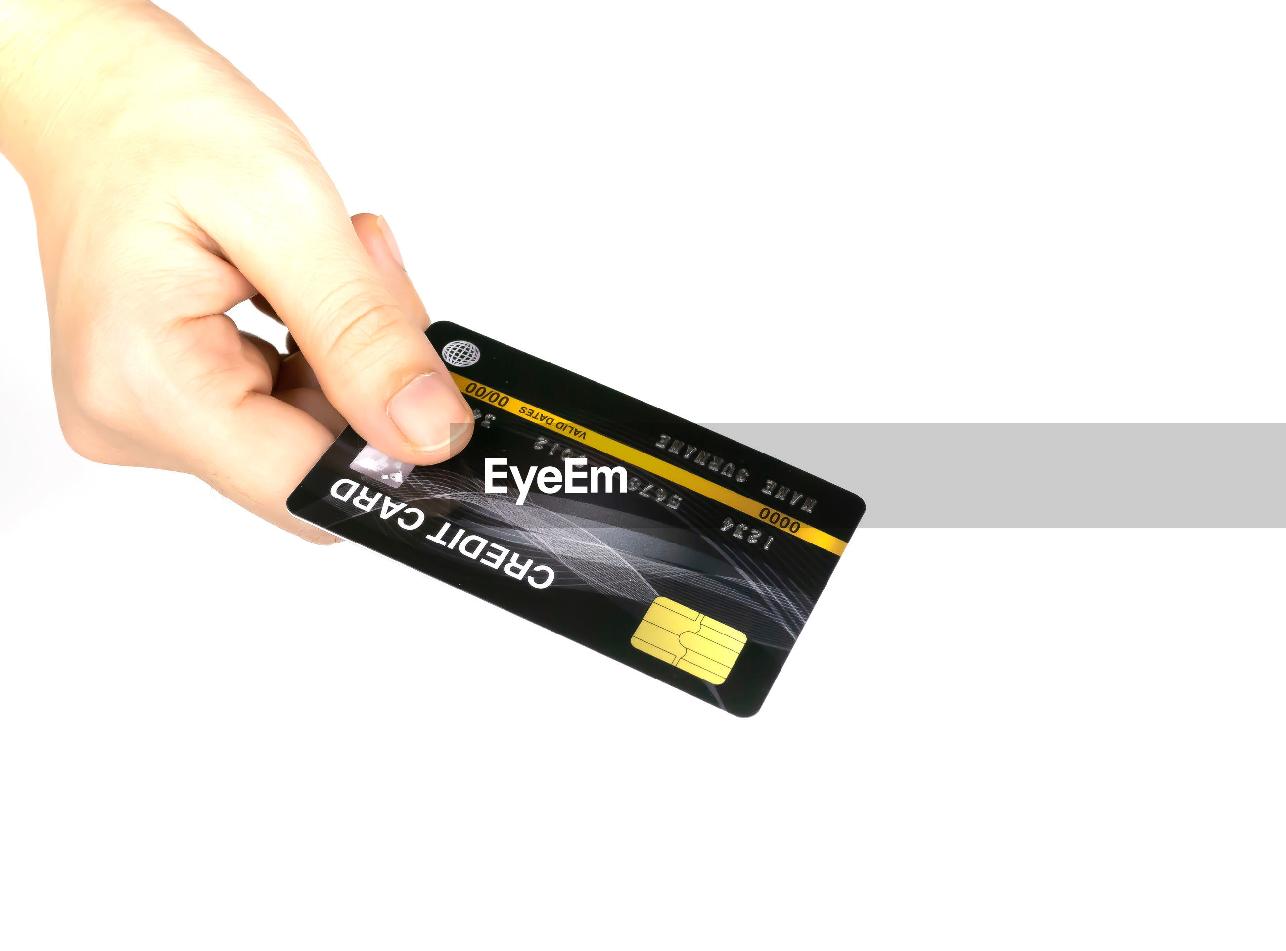Cropped hand of person holding credit card against white background