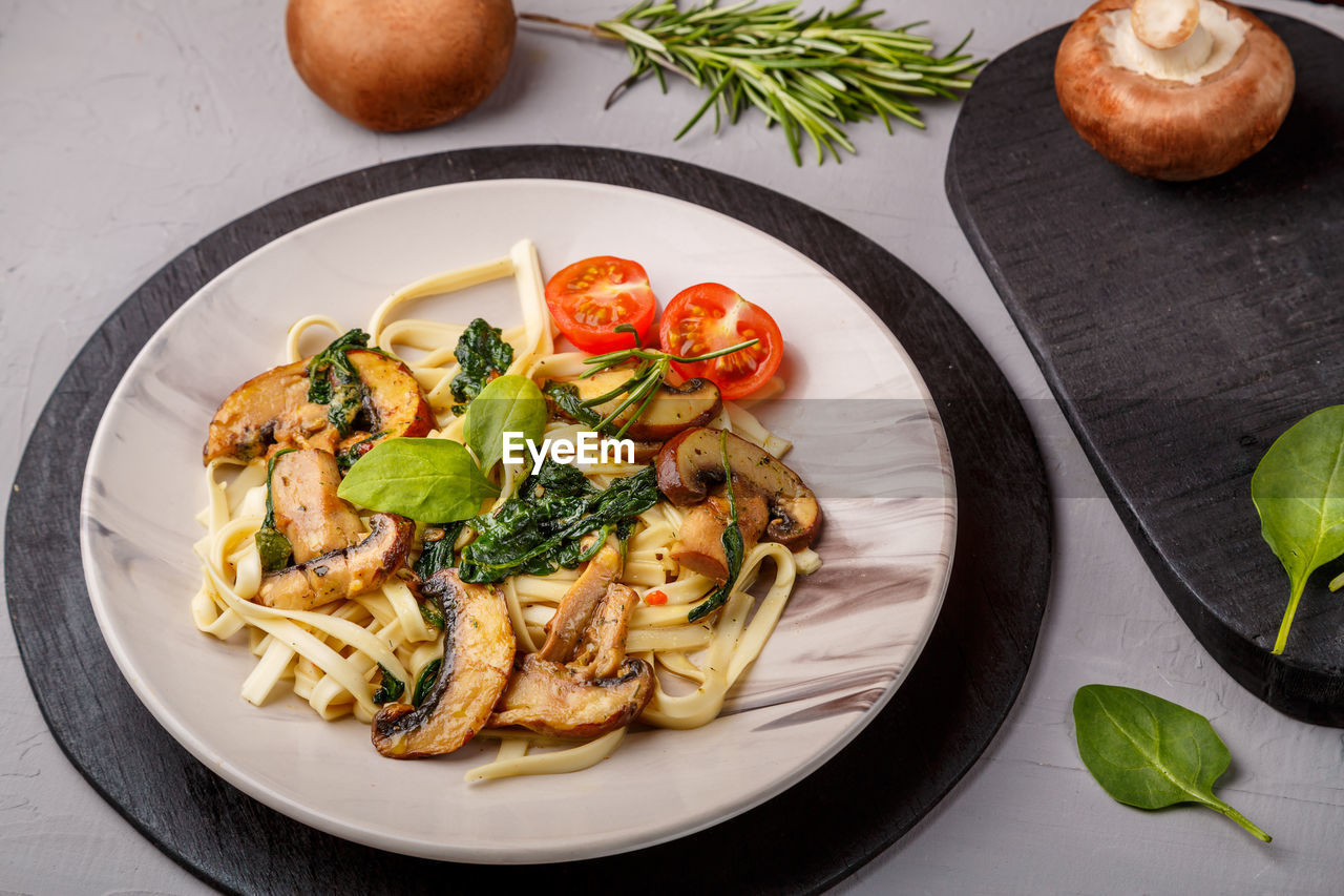 Udon with mushrooms and spinach in a plate on a napkin on a concrete background near mushrooms