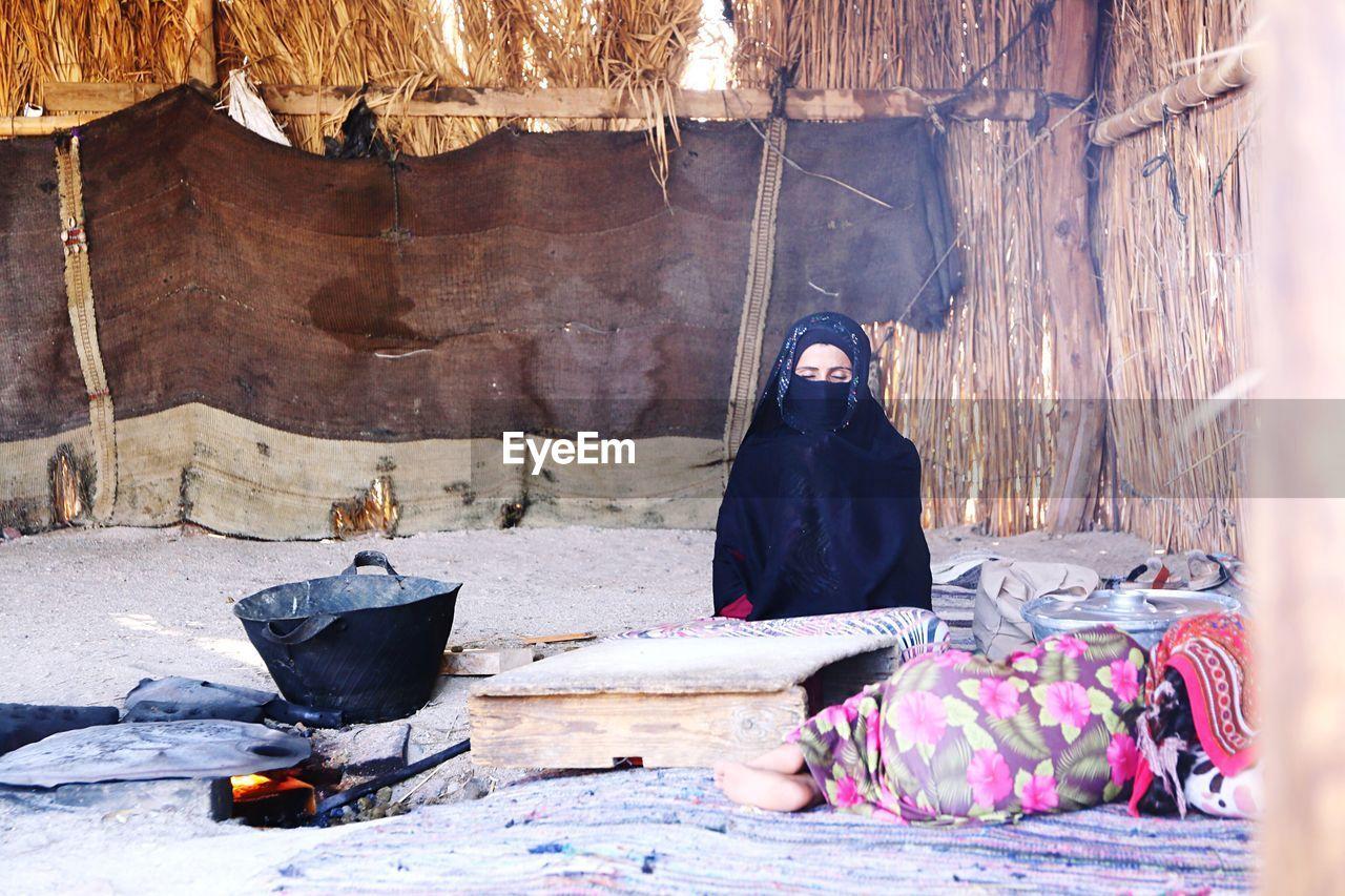 Woman Sitting In Hut