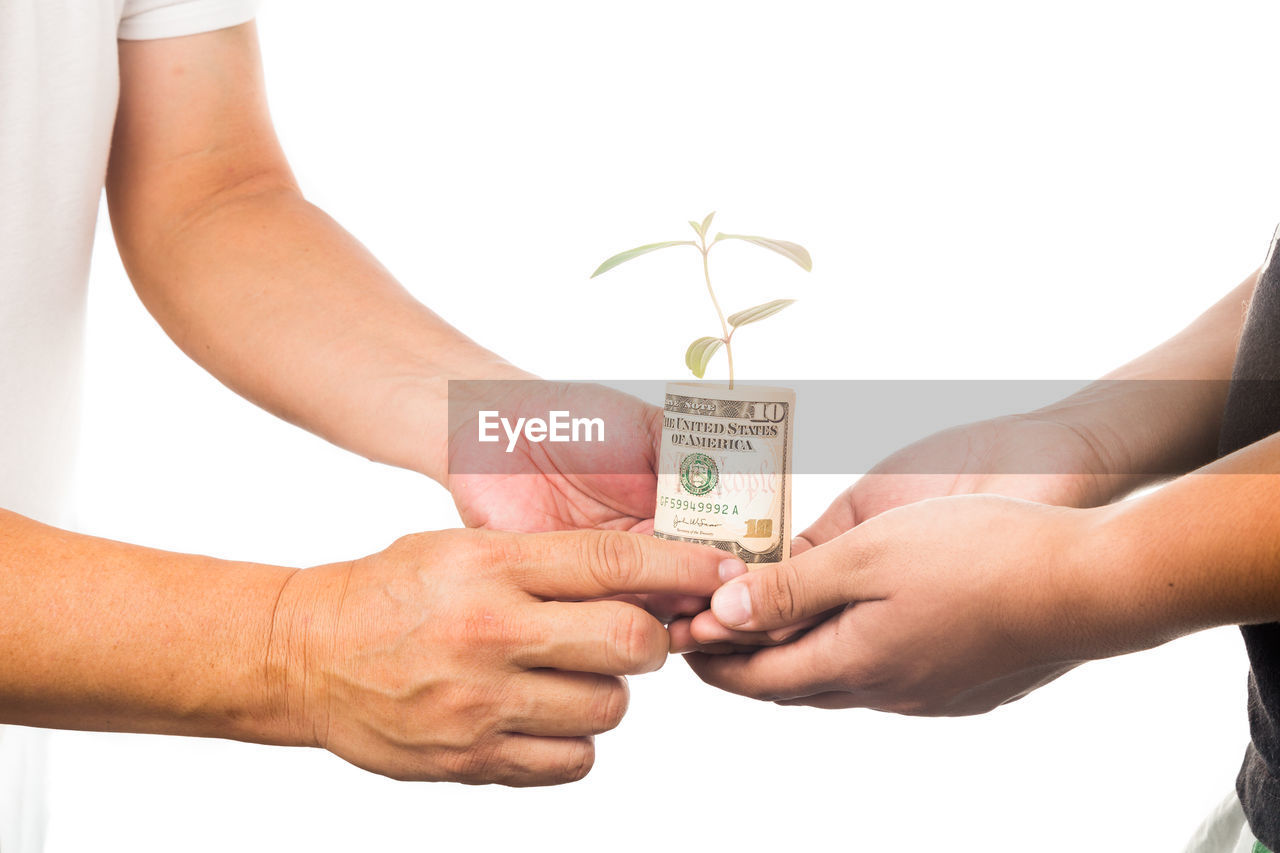 human hand, hand, finance, human body part, studio shot, currency, holding, white background, indoors, business, paper currency, people, savings, two people, adult, close-up, wealth, giving, men, body part, human limb, receiving, care, finger