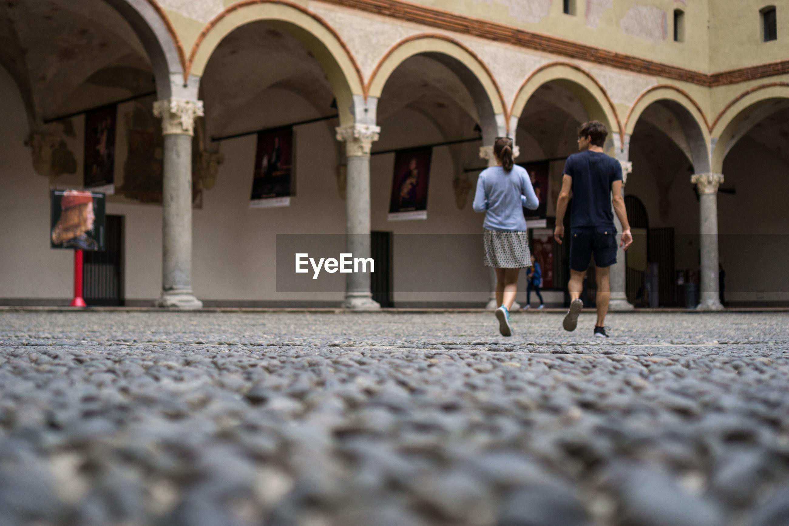 Rear view of tourist walking in courtyard in castello sforzesco