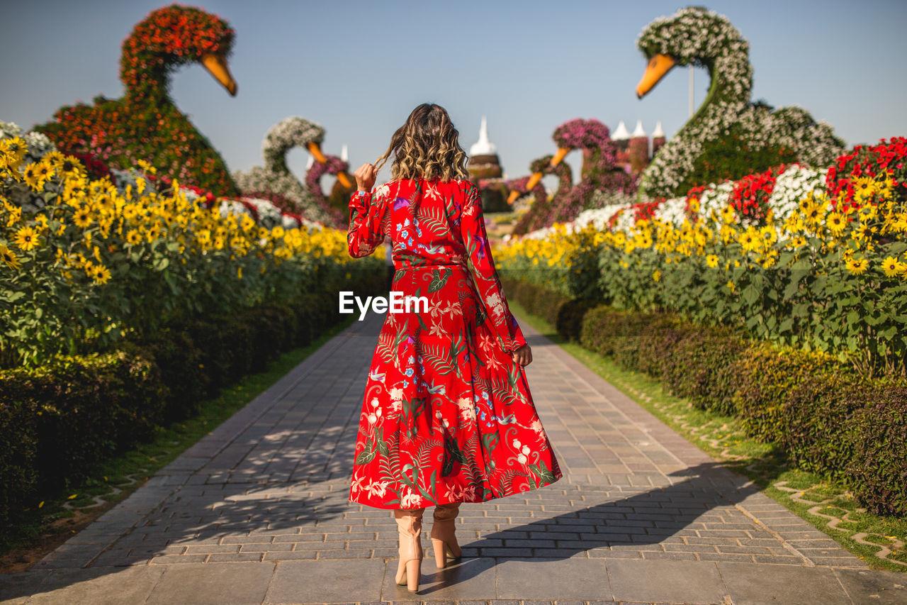 Rear view of woman in red dress walking on footpath amidst flowering plants in park