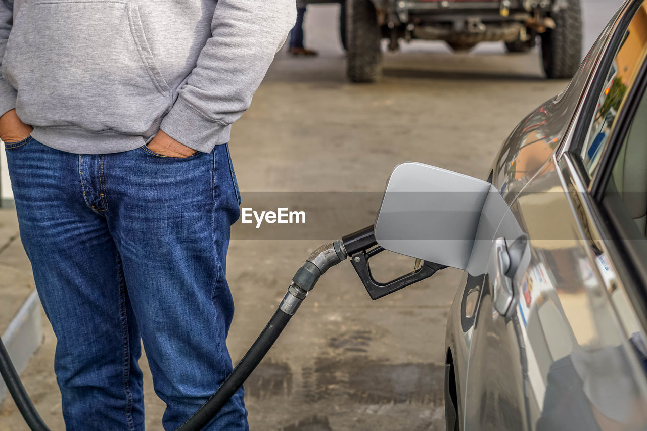 Midsection of man standing by car at fuel station