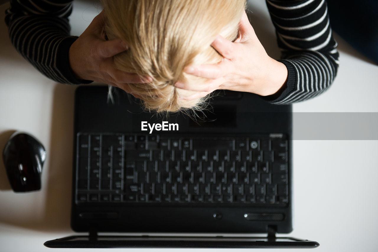 Tensed Woman Using Laptop At Desk