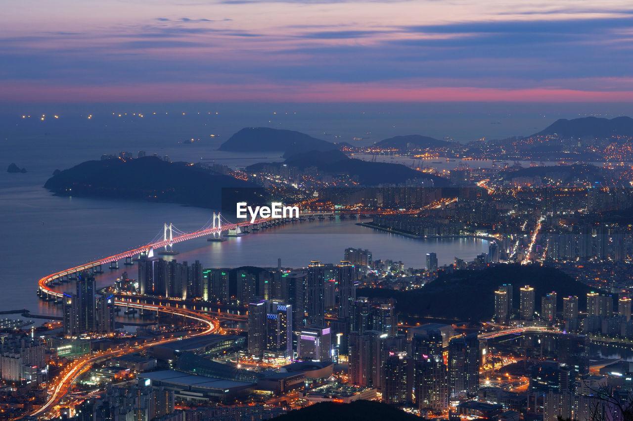 Aerial view of gwangandaegyo over sea by illuminated cityscape during sunset
