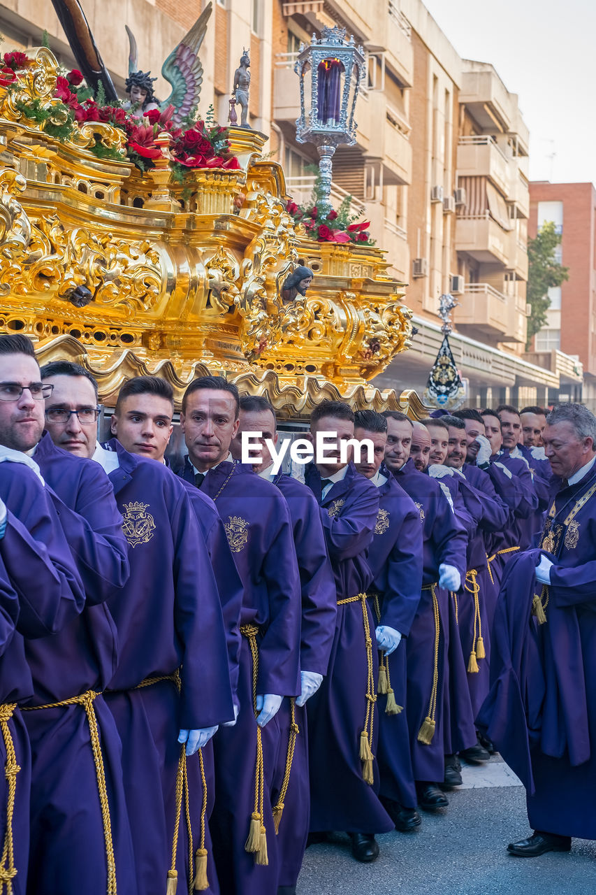 real people, group of people, large group of people, crowd, architecture, men, built structure, clothing, building exterior, city, celebration, day, women, togetherness, adult, standing, traditional clothing, lifestyles, outdoors, uniform, marching