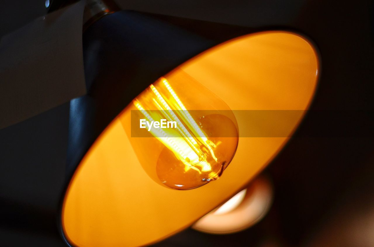 illuminated, orange color, yellow, lighting equipment, light bulb, close-up, electricity, glowing, no people, technology, indoors, light - natural phenomenon, light, electric light, focus on foreground, filament, electric lamp, glass - material, domestic room, low angle view, electrical equipment