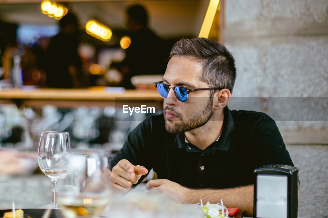 Man Wearing Sunglasses Sitting At Restaurant