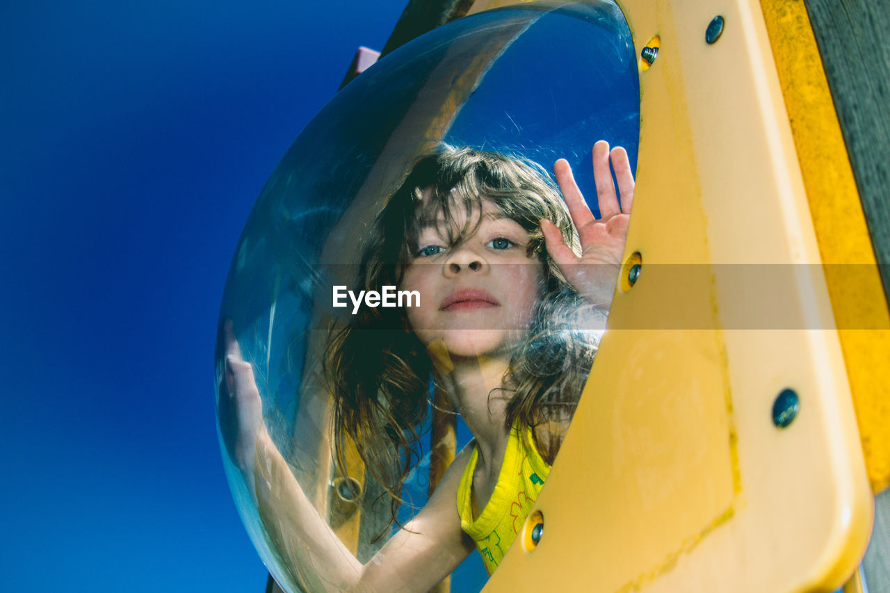 Low Angle Portrait Of Girl Looking Through Glass Against Clear Blue Sky