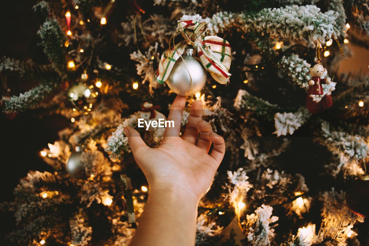 Cropped hand of woman touching illuminated christmas tree