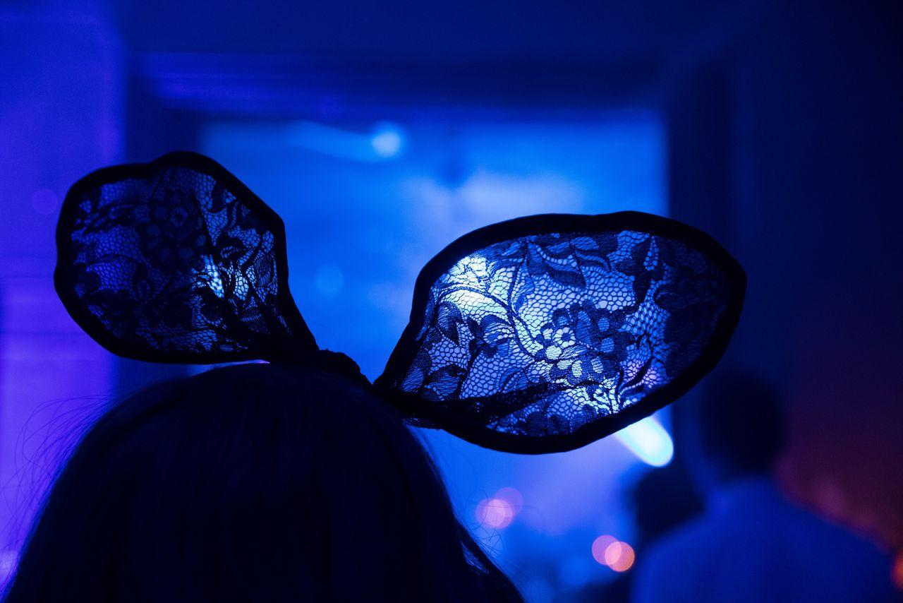 Close-up of woman wearing headwear in illuminated nightclub