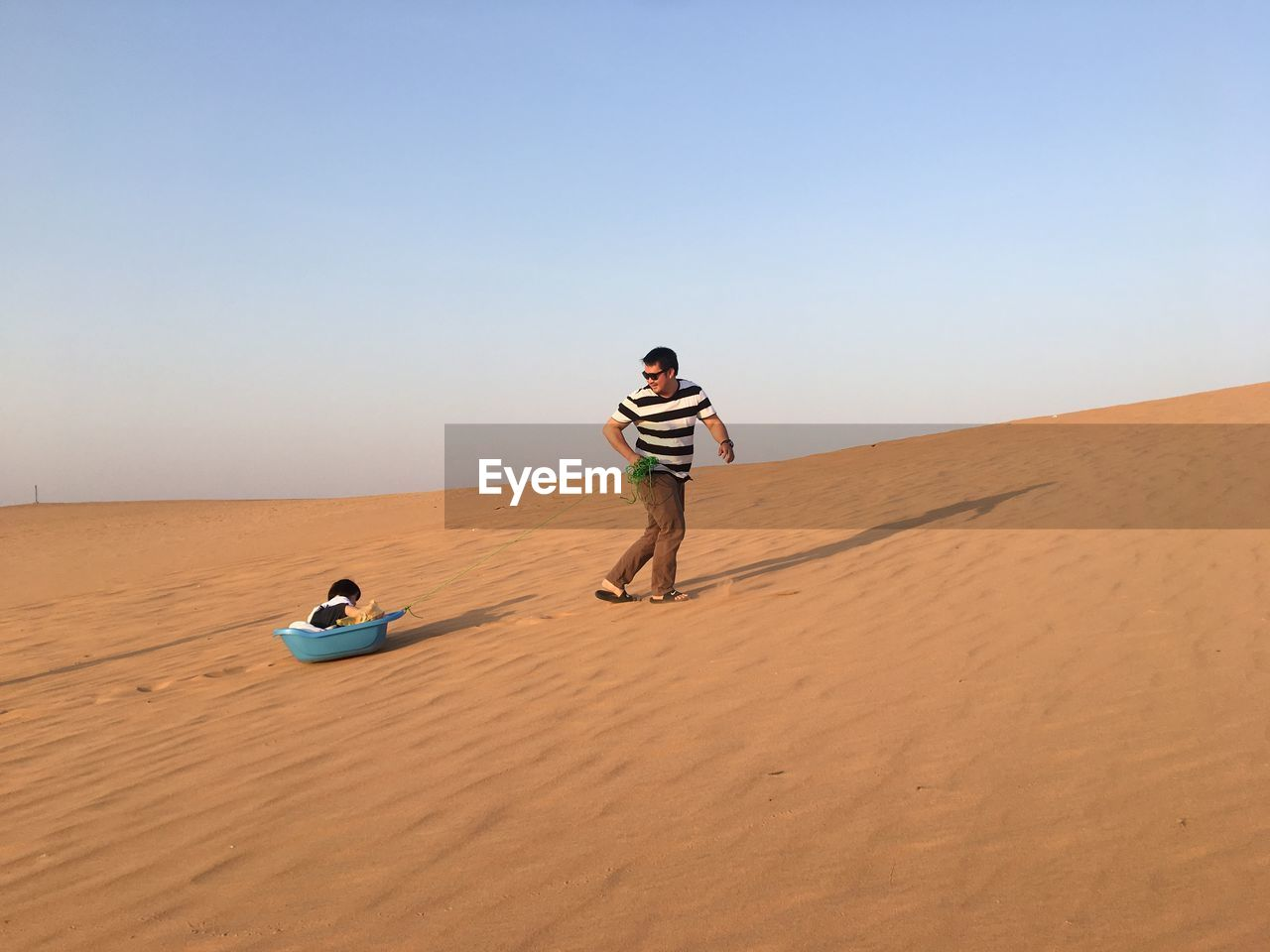 land, sky, sand, desert, real people, lifestyles, sand dune, scenics - nature, leisure activity, climate, arid climate, beauty in nature, full length, landscape, copy space, nature, clear sky, people, casual clothing, day