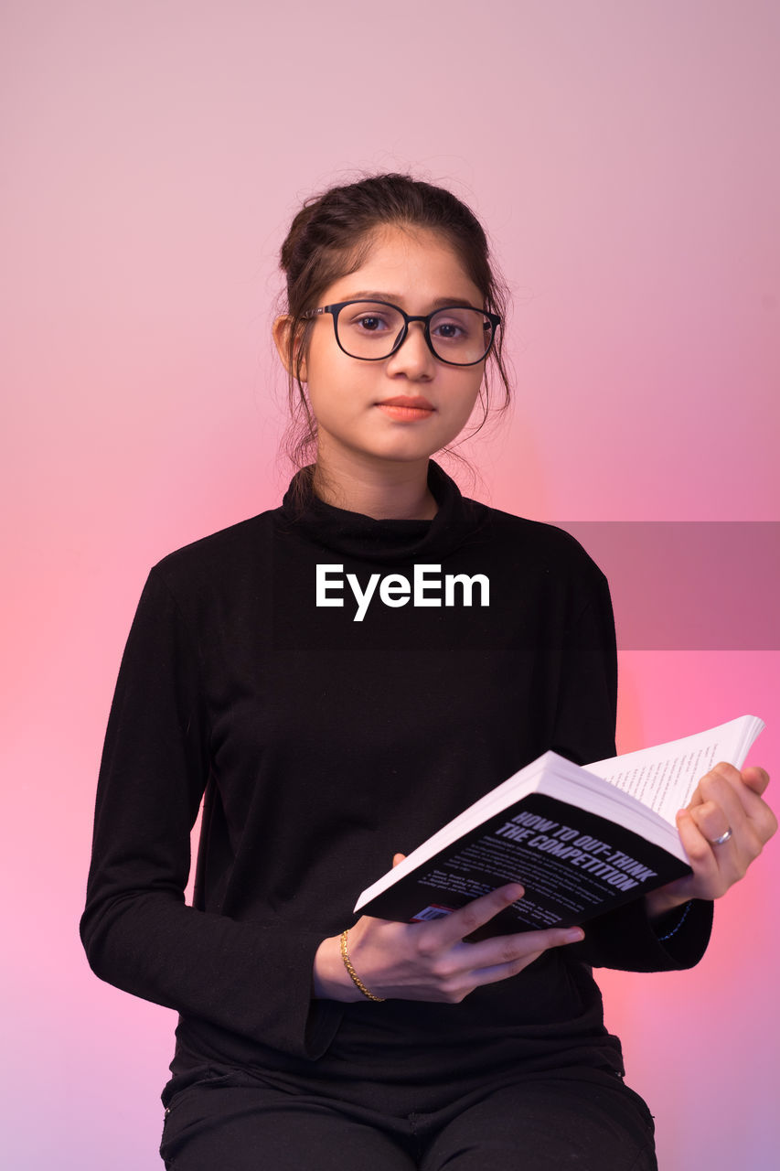 looking at camera, eyeglasses, glasses, front view, one person, portrait, indoors, holding, studio shot, three quarter length, young adult, casual clothing, women, colored background, pink background, real people, waist up, wireless technology, hairstyle, teenager