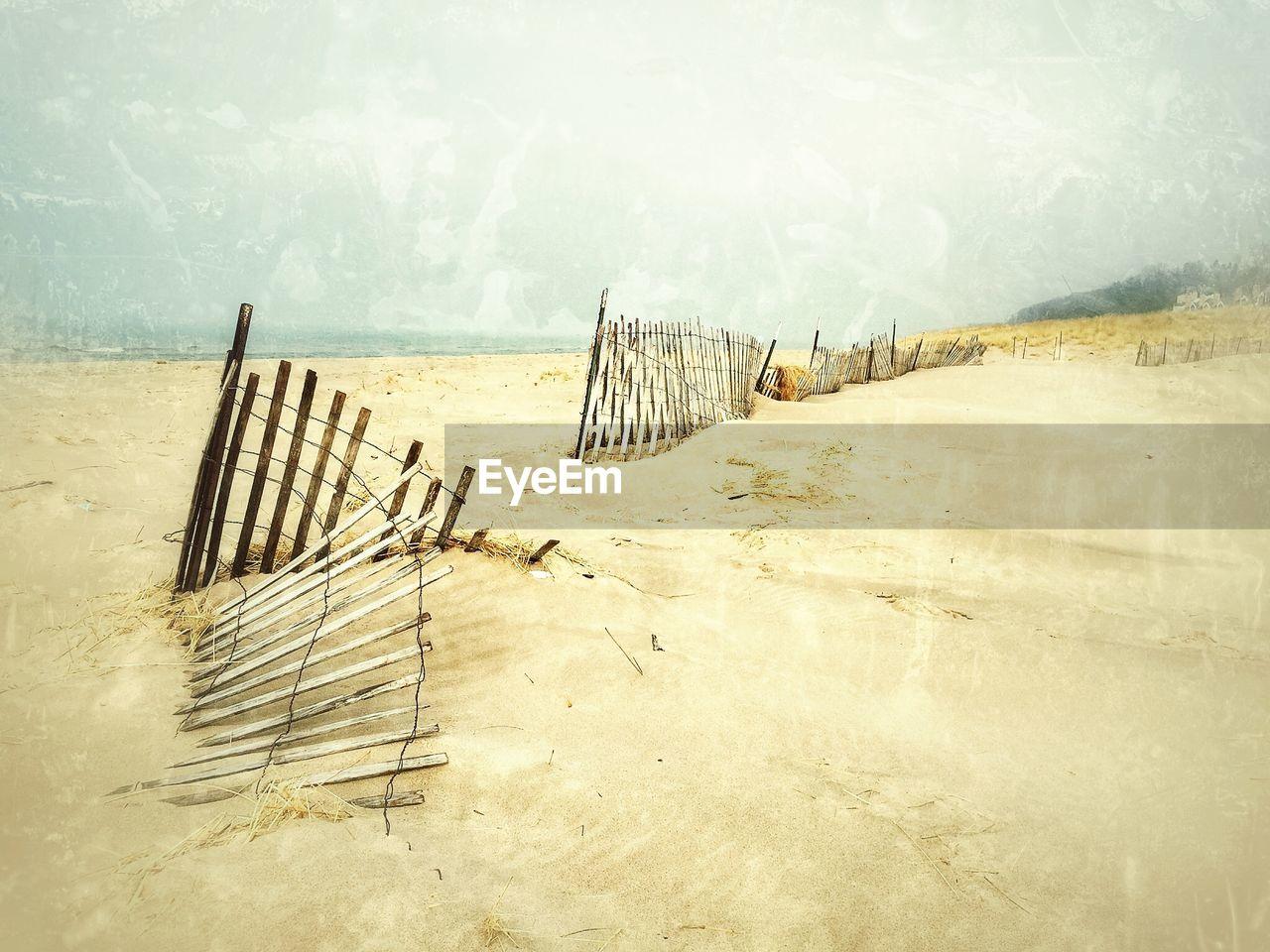 Damaged railing on beach against sky