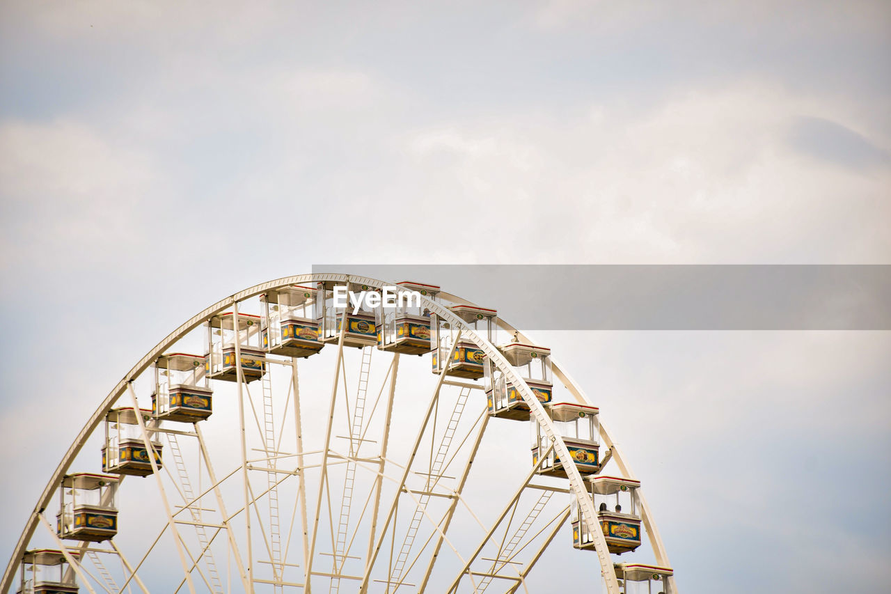 LOW ANGLE VIEW OF FERRIS WHEEL AGAINST CLOUDS