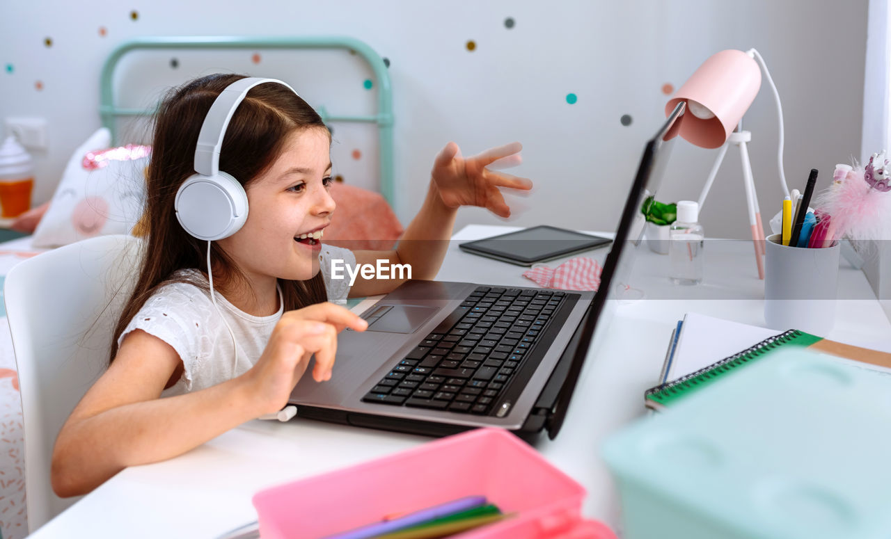 YOUNG WOMAN USING SMART PHONE WHILE SITTING IN LAPTOP