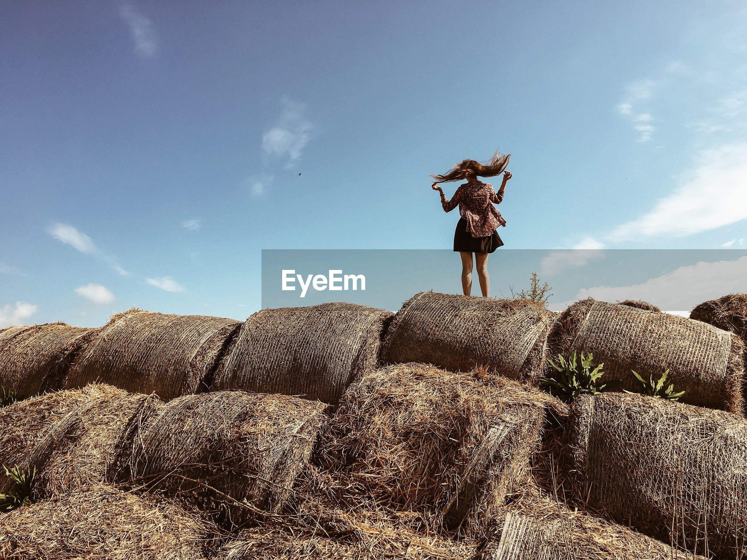 Rear view of woman jumping on hay bales stack against sky