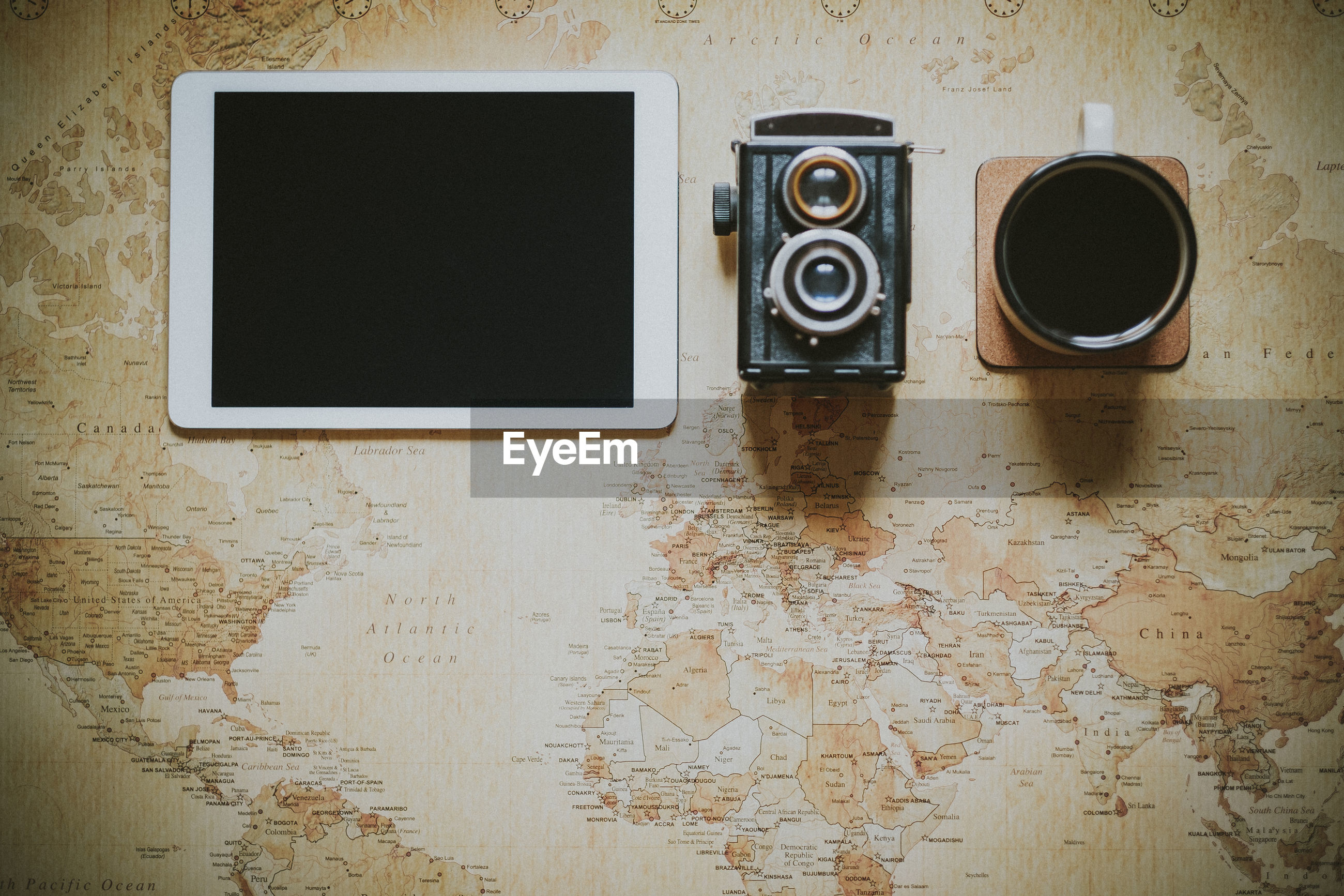 Directly above shot of digital tablet with vintage camera and coffee on world map