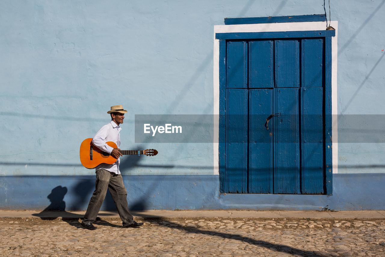 MAN HOLDING UMBRELLA WHILE STANDING AGAINST DOOR
