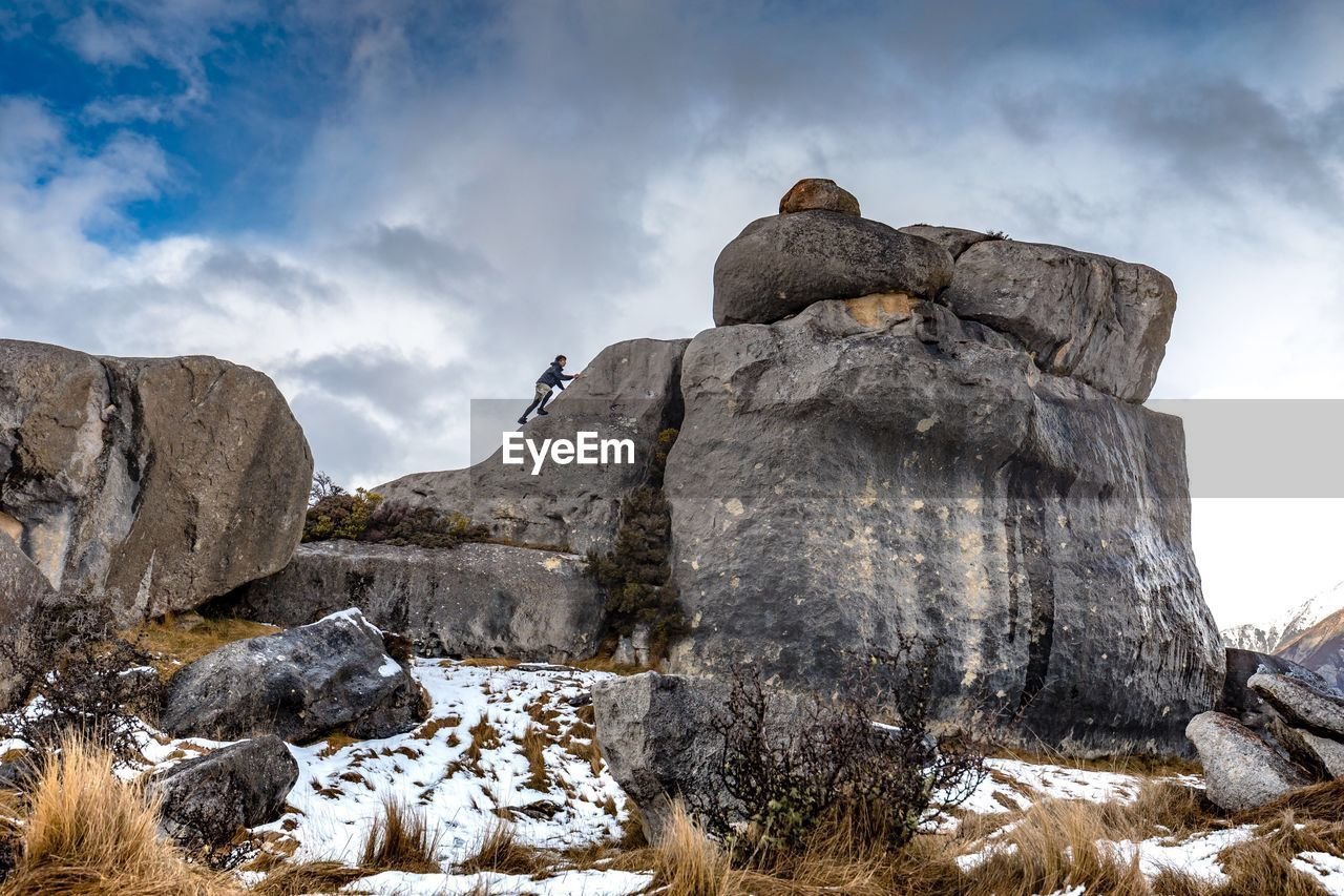 Low angle view of man climbing rock against sky