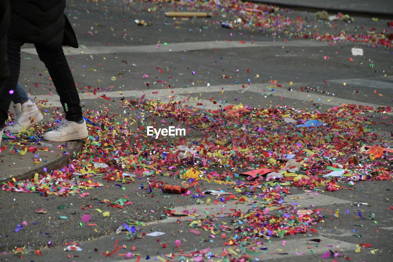 Low section of people walking by confetti on street