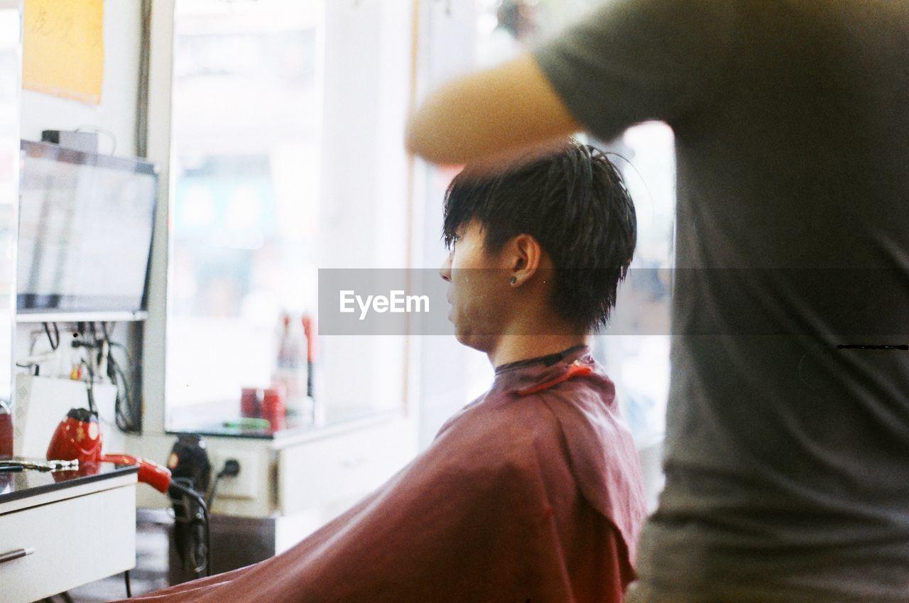 Barber Cutting Man Hair At Salon