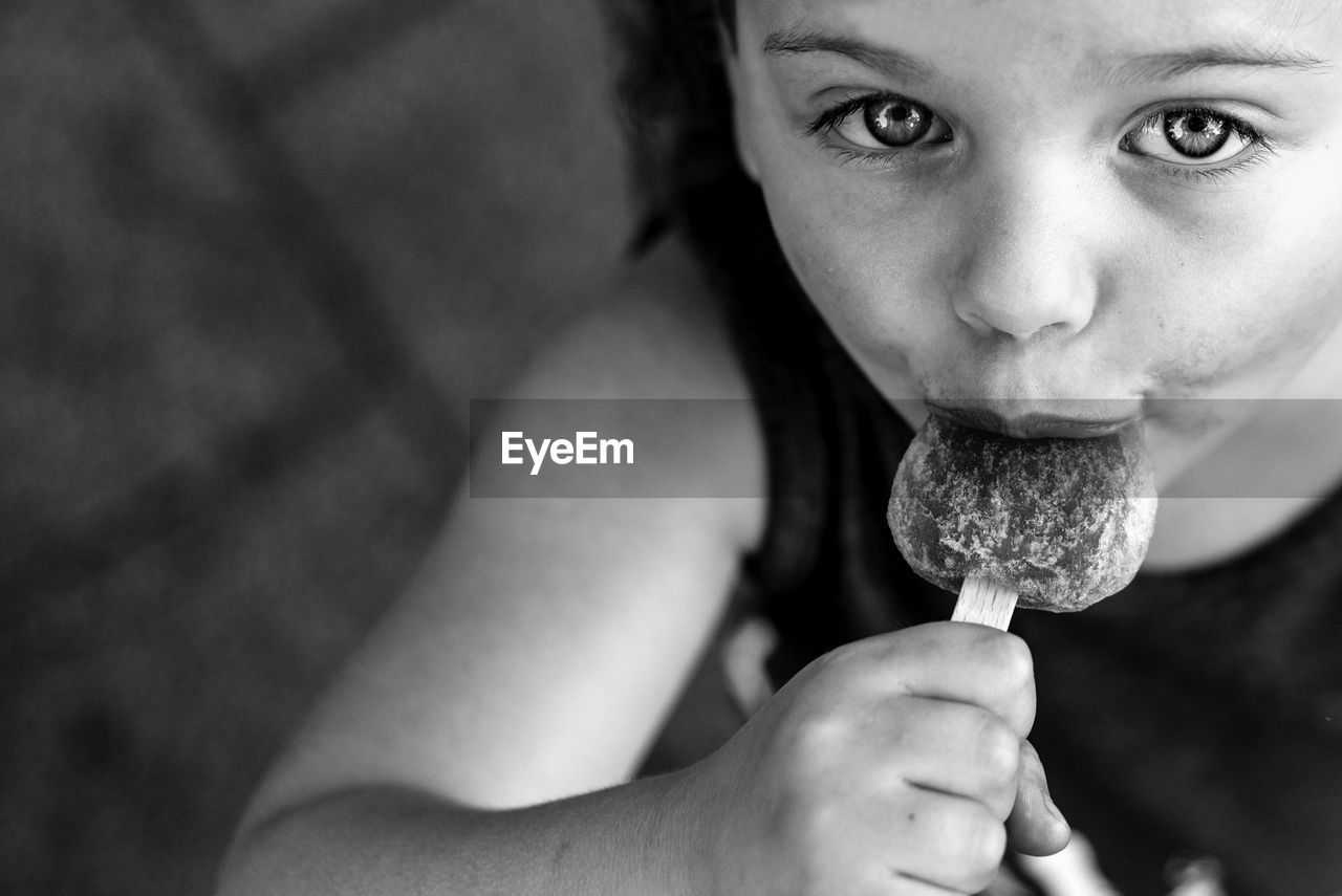 Close-Up Portrait Of Girl Eating Ice Cream